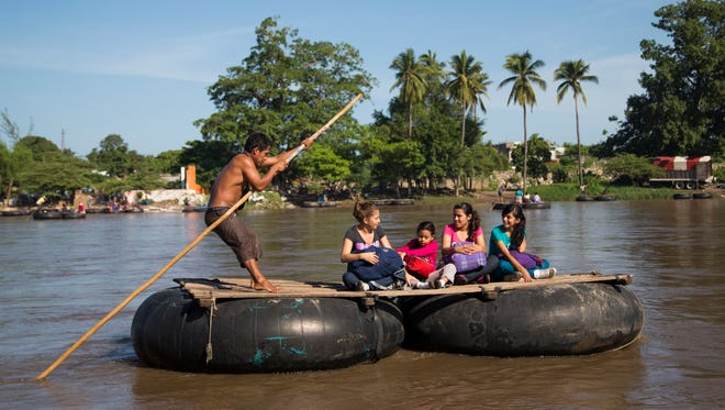 Migrants who appeared to be using coyotes illegally cross into Mexico from Guatemala using a raft on the Suchiate River June 21, 2014. Crime and lack of jobs have sent people from Central America to the U.S. including unaccompanied minors in increasing numbers.