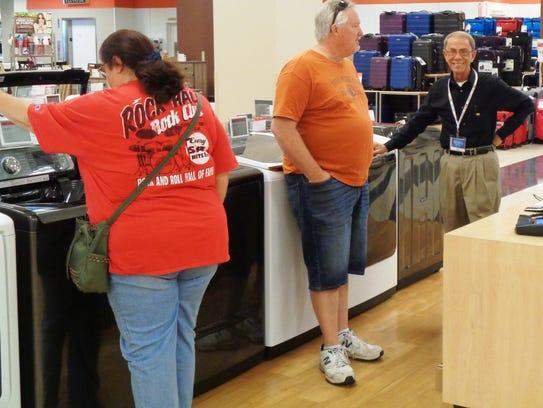 Ben Barrett assists customers Steve and Debbie Schwantes