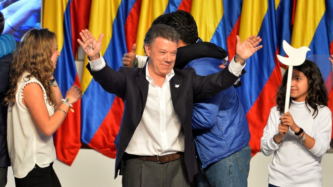 President Juan Manuel Santos celebrates his victory in the presidential runoff at his campaign headquarters in Bogota, Colombia, on Sunday. Santos defeated challenger Oscar Ivan Zuluaga, of the Democratic Center, and won a second four-year term.