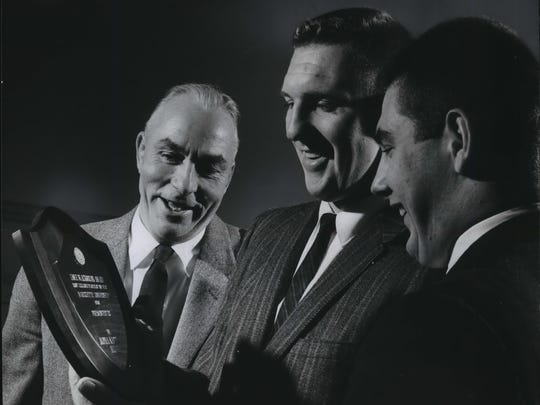 Former Marquette football tackle Jeff Messerknecht (center) admires his 1960 team MVP trophy along with coach Lisle Blackbourn (left) and quarterback Joe Schultz.