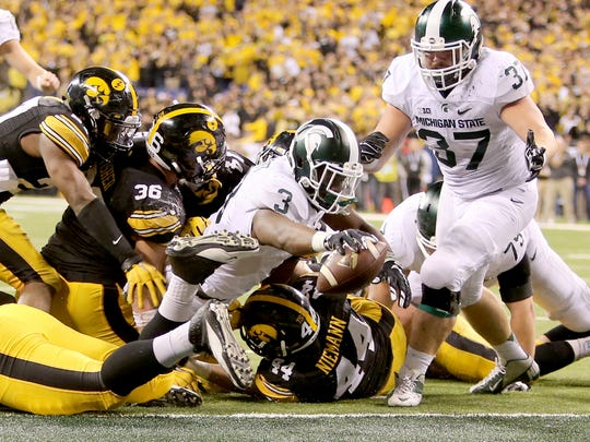 Michigan State Spartans running back LJ Scott (3) dives in for a touchdown during the fourth quarter of the Big Ten Conference football championship game against the Iowa Hawkeyes at Lucas Oil Stadium in Indianapolis. Michigan State defeated Iowa 16-13.