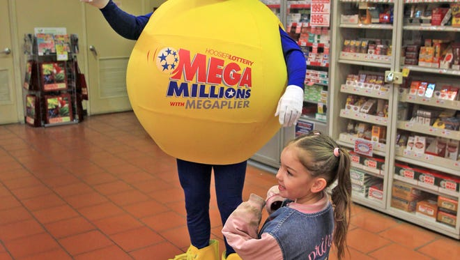 Brooklyn Harper looks at the Mega Millions mascot as the Hoosier Lottery gives out free Mega Millions tickets Dec. 3, 2013, at Marsh Supermarket, 3633 Kentucky Ave., Indianapolis.