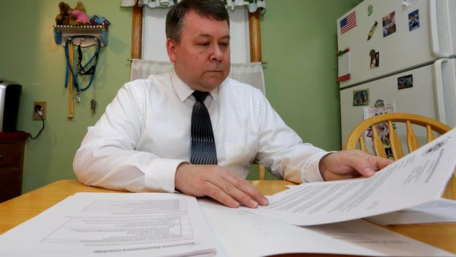 Kevin Nyklewicz, a deputy inspector for the Milwaukee County Sheriff's Office, reviews pension plan documents at his kitchen table. He was planning to retire March 10 until he was told the retirement office made a mistake.