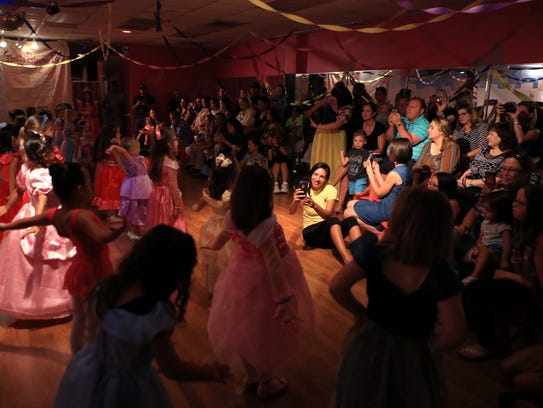 Families of tiny princesses watch their children perform