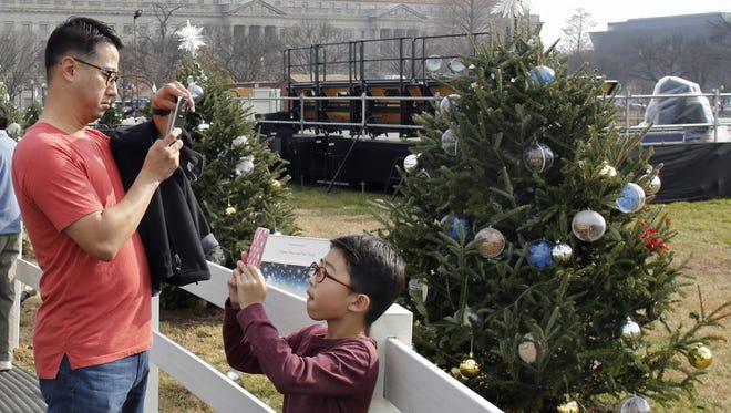 People enjoy unusual warm weather near the National Christmas tree in Washington on Dec. 11, 2015.