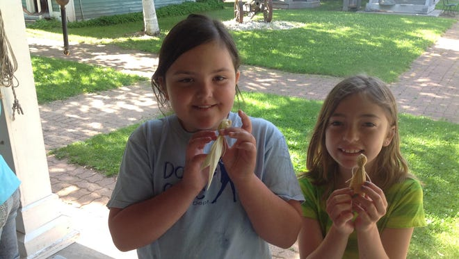 Ava Ehrhardt and Hailey Wessels of Fond du Lac display the corn husk dolls they created during a summer field trip to Galloway House & Village.