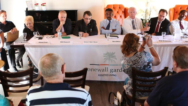 Palm Springs mayoral candidates (from left) Guy Burrows, Ginny Foat, Erbil Gunasti, Rob Moon, Ron Oden, Mike Schaefer, Bob Weinstein and Ricky Wright participate in a forum at the Stonewall Gardens Assisted Living facility in Palm Springs on Wednesday.