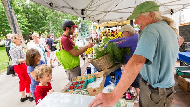 Blue Valley Gardens farmer Matt Smith, right, talks with Kaz Dooley, 5 as his father Larry Dooley purchases fennel from George Hesselberg at the Dane County Farmers' Market in Madison, Wis.