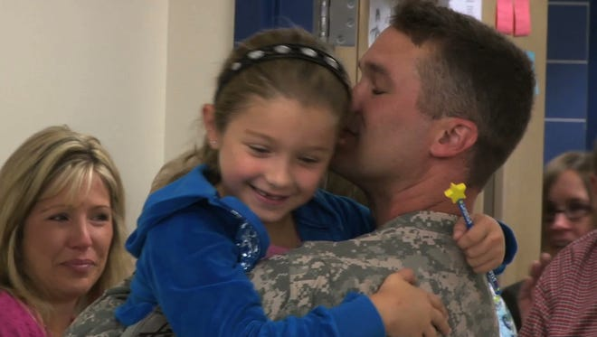 Senior Chief John Martin, right, a Navy Reservist, surprises his daughter, Taryn, on her eighth birthday Sept. 28, 2011, after he served a year overseas. Tricia Martin is at left.