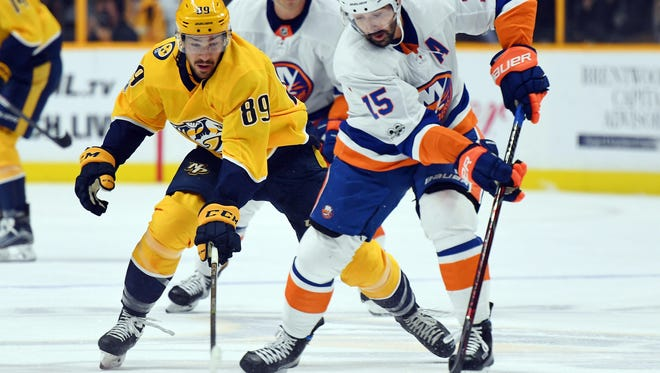 Oct 28, 2017; Nashville, TN, USA; New York Islanders right wing Cal Clutterbuck (15) keeps the puck from Nashville Predators center Frederick Gaudreau (89) during the first period at Bridgestone Arena.