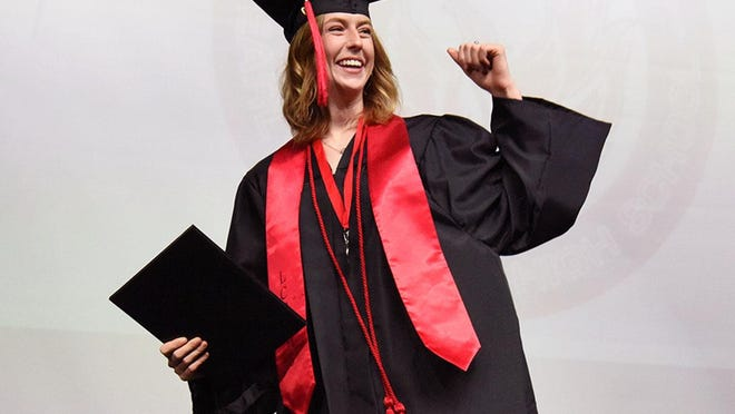 Grace Mae Benson allows herself a small celebration after accepting her diploma during the commencement exercise at Lenoir County Early College High School on Monday.