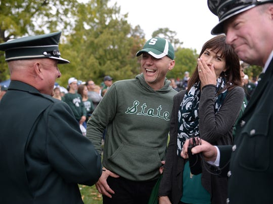 From left to right, Glen Brough, visual and field coordinator, former Spartan Marching Band members Steve and Sarah Linley and John Madden, Spartan Marching Band director, chat before the homecoming game against Northwestern on Oct. 15, 2016 at Adams Field at Michigan State University in East Lansing.