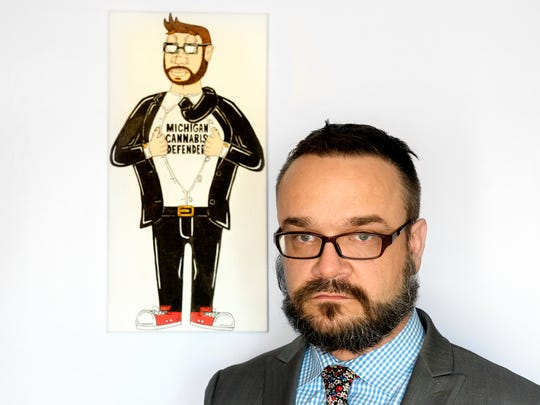 """Lansing lawyer Josh Covert specializes in cannabis law. Covert is shown in his office on Monday, Nov. 20, 2017, next to a painting a friend made depicting Covert pulling back his clothes to expose a super hero shirt that reads """"Michigan Cannabis Defender."""""""