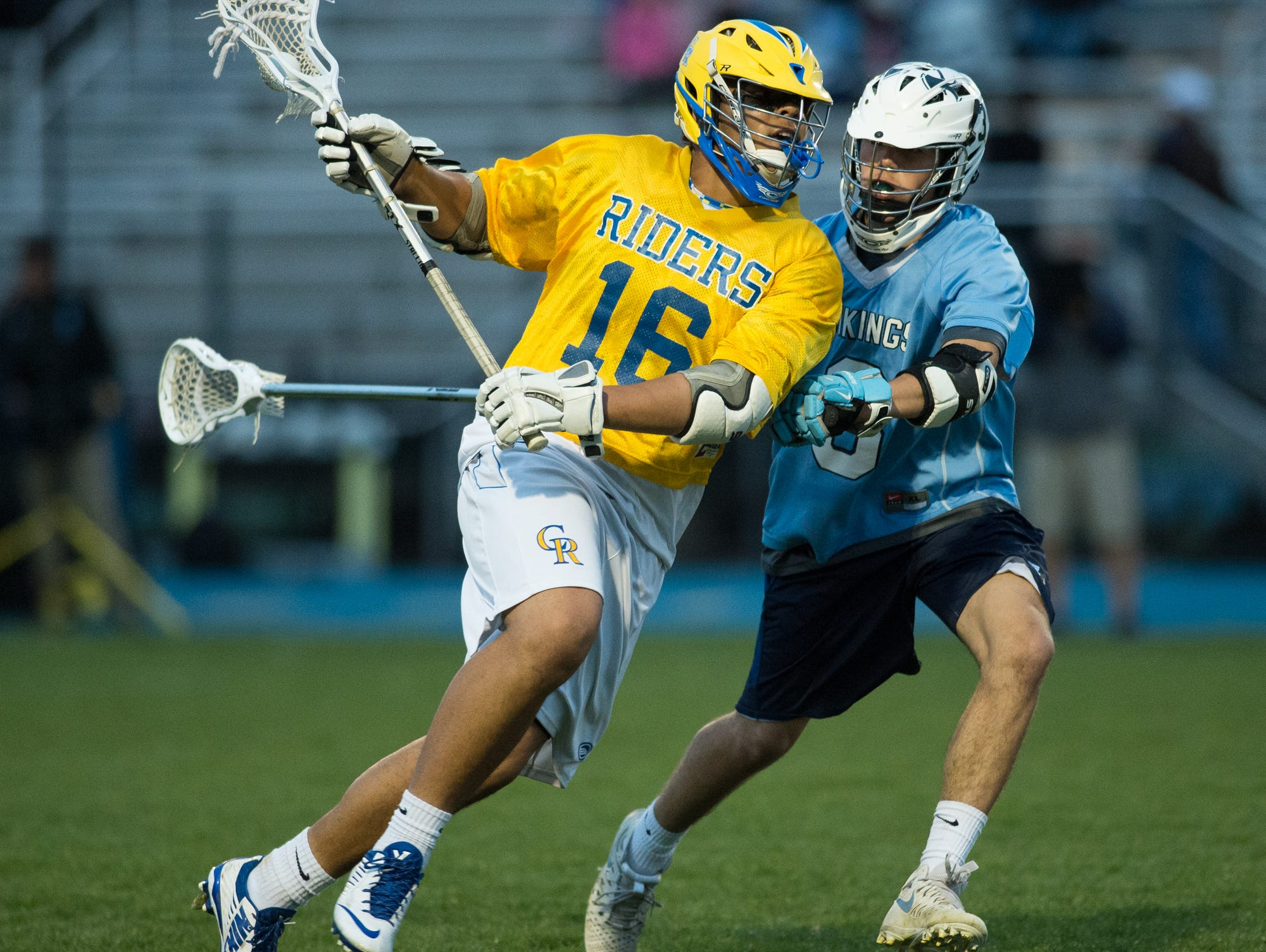 Caesar Rodney's Demetrius Stevenson (16) runs down the field while being defended by Cape Henlopen's Dillon Mocci (3).