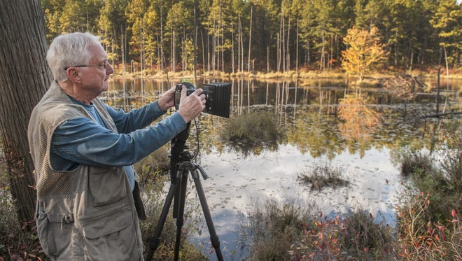 Photographer Al Horner of Medford Lakes captures a forert image and its reflection in a river in Wharton State Forest in Tabernacle.  Horner made art of PInelands scenery and has published a book of his work.