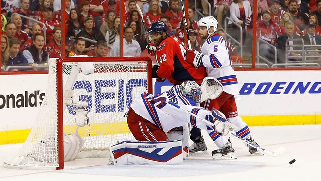 Washington Capitals right wing Joel Ward (42) and New York Rangers defenseman Dan Girardi (5) battle for the puck in front of Rangers goalie Henrik Lundqvist (30) in the second period in game four of the second round of the 2015 Stanley Cup Playoffs at Verizon Center.