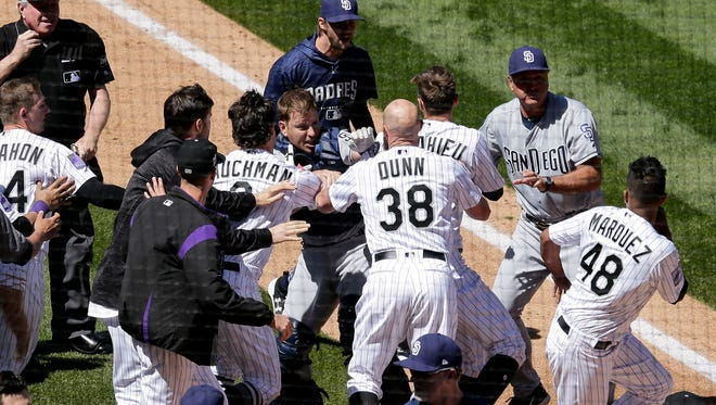 San Diego Padres catcher A.J. Ellis (17) and Colorado Rockies second baseman DJ LeMahieu (9) fight after a play in the third inning at Coors Field.
