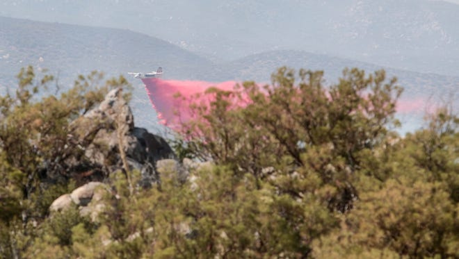A plane drops fire retardant on the Ribbon Fire burning East of the Cranston Fire on Thursday, July 26, 2018.