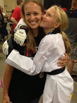 Natalie Hershberger hugs her mom, Nicole, after a taekwondo competition. The two are collaborating on an illustrated book for small children.