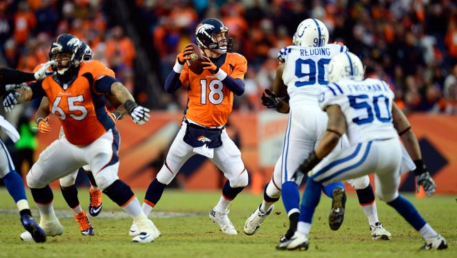 Jan 11, 2015; Denver, CO, USA; Denver Broncos quarterback Peyton Manning (18) looks to pass against the Indianapolis Colts during the second quarter in the 2014 AFC Divisional playoff football game at Sports Authority Field at Mile High.