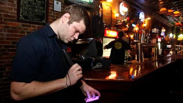 Finnegans Wake door man CJ Neal checks an ID of a bar patron as they enter the bar on Wednesday, Jan. 28, 2015.