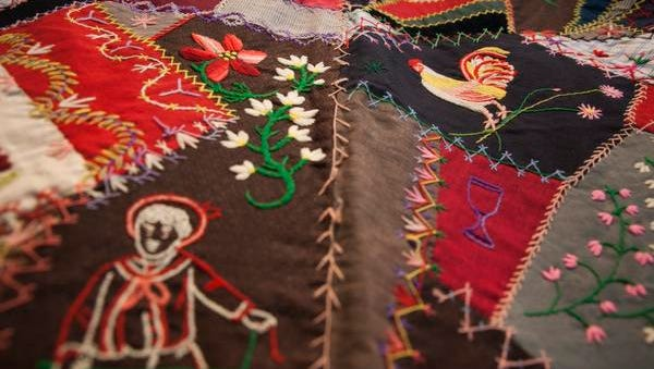 Details of a small child, flower and rooster decorate a quilt on display as part of an exhibit showing four generations of Yount family quilts at the R.R. Smith Center for History & Art.