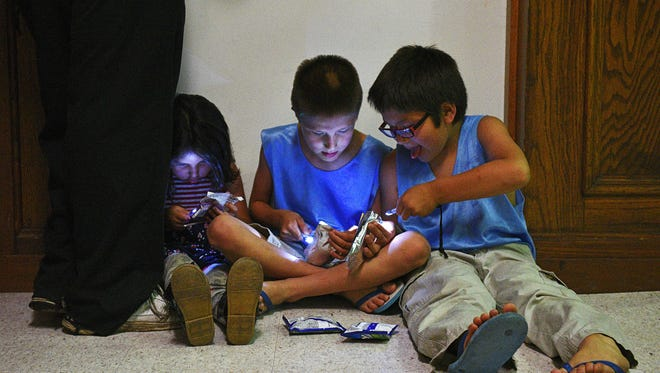 Aryanna Creek, 4, left to right, Devontae Johnson, 8, and Lamontae Johnson, 6, play with flashlights as their mom Brenda Creek fills out paperwork during a PCs for People computer giveaway event Wednesday, June 8, 2016, at the Multi-Cultural Center in Sioux Falls. The event, put on by PCs for People and Midco, provided 75 free computers for low-income families.