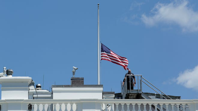 Personnel leave after lowering the U.S. flag to half-staff at the the White House following President Obama's statement on the mass shooting at an Orlando, Fla., nightclub on June 12, 2016.