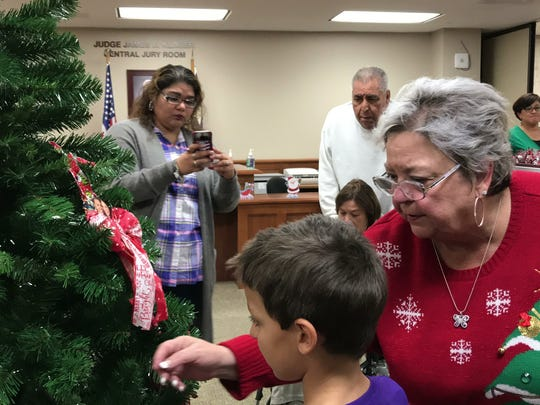 Donna Watkins, of the Homicide Survivors Group, places an ornament on the Tree of Angels at the Nueces County Courthouse on Wednesday, Dec. 6, 2017.