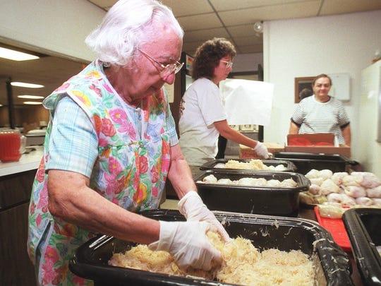 In this 1997 archive photo, Margie Herz picks up two hands full of Sauerkraut to prepare for the Ohio Sauerkraut Festival in Waynesville.
