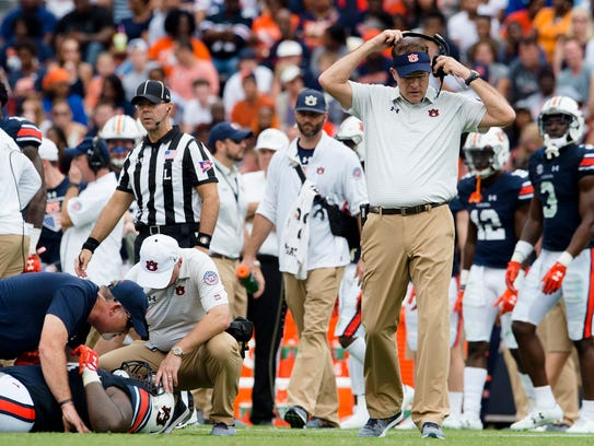 Auburn head coach Gus Malzahn goes to check on Auburn