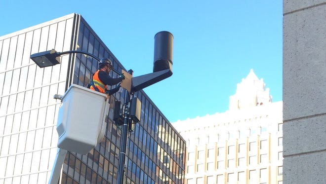 """A contractor installs a Verizon """"small cell"""" device that will help expand 4G LTE capacity for phone service in downtown Des Moines."""
