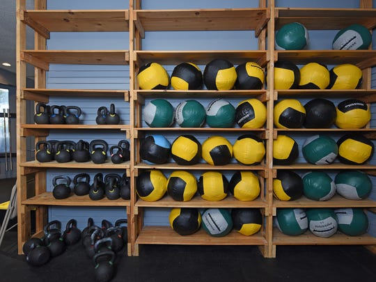 Kettle bells and medicine balls fill shelves at Crossfit