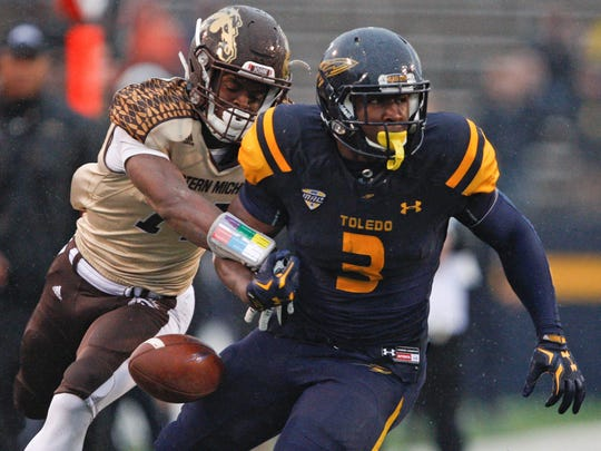 In this Nov. 27, 2015 photo, Western Michigan Broncos cornerback Darius Phillips (14) knocks the ball away from Toledo Rockets running back Kareem Hunt (3) during the fourth quarter at Glass Bowl. Broncos win 35-30.