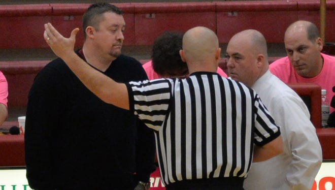 A referee talks to Riverdale coach Cory Barrett, left, and Smyrna coach Shawn Middleton during the Lady Bulldogs win over Riverdale on Saturday