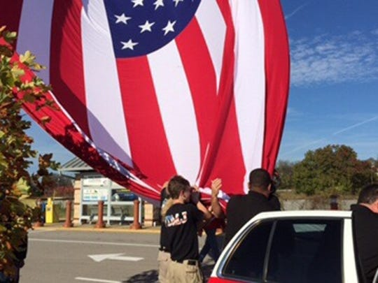 Firefighters load a 30-by-60-foot American flag recently