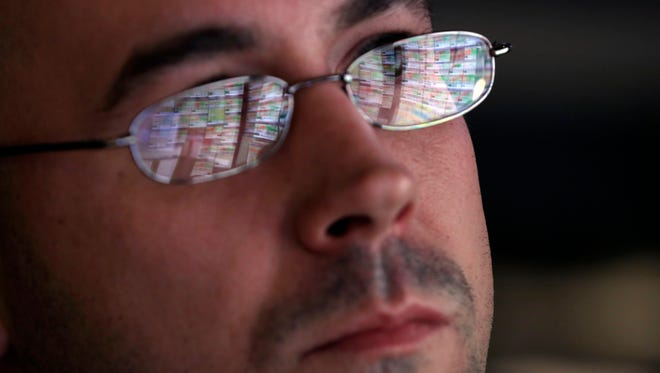 The screens of specialist Jarret Johnson are reflected in his glasses as he works at his post on the floor of the New York Stock Exchange.