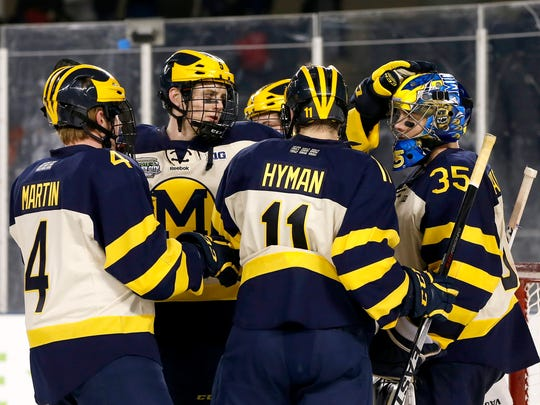 East Lansing High grad Cutler Martin (4) celebrates with Michael Downing (5), Zach Hyman (11) and Zach Nagelvoort (35) after Michigan's 4-1 win over MSU on Saturday at Soldier Field in Chicago.
