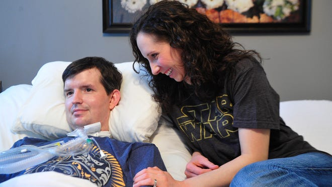 Nathan Ashley and his wife, Kathleen Ashley, share a moment in their home Friday.