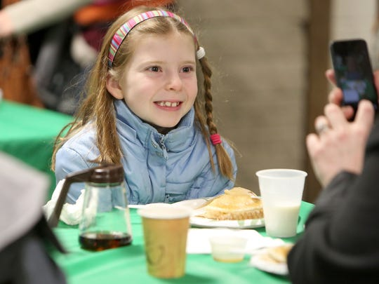 Natalie Johnson of Anderson Township smiles for a photo as she eats her breakfast during a previous Pancakes in the Woods event held at California Woods Nature Preserve.