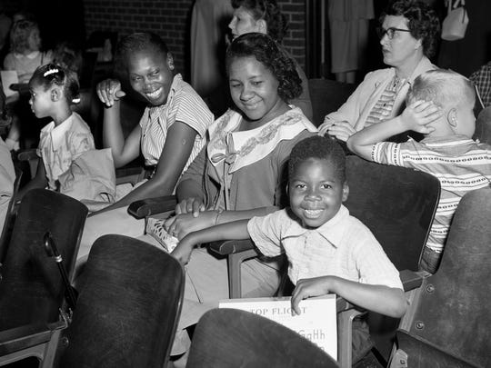 First grader Marvin Moore, right, is all smiles as his mother, Maude Baxter, and Mary Louise Watson, with her daughter Barbara Jean, left, look on Sept. 9, 1957. They are waiting in the auditorium of the all-white Jones School to be two of four students to integrate it on first day of school.