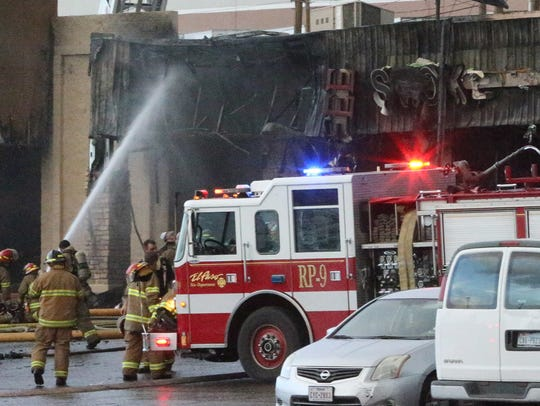 Firefighters extinguish smoldering areas of a business