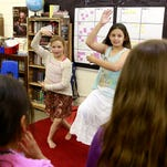 Fifth-graders Mariah Flores, left, and Diamond Nez talk about the report they compiled on Switzerland during Multicultural Day on Thursday at Apache Elementary School.
