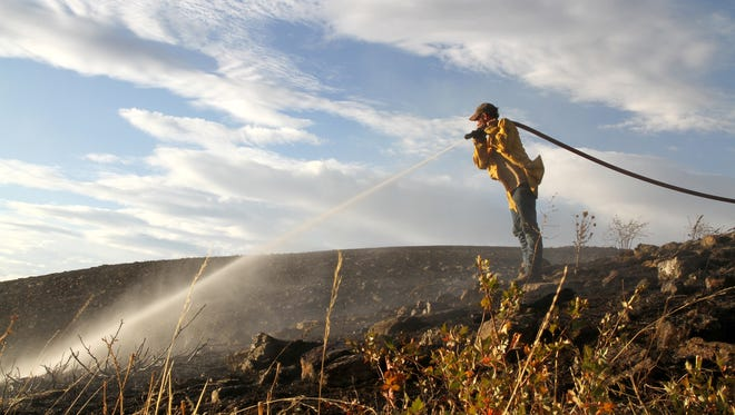 A Sand Coulee firefighter soaks down grass to prevent the spread of a fire. Fire board trustees could notbe an employee or a volunteer firefighter of fire districts,under new trustee eligibility requirements proposed by Cascade County.