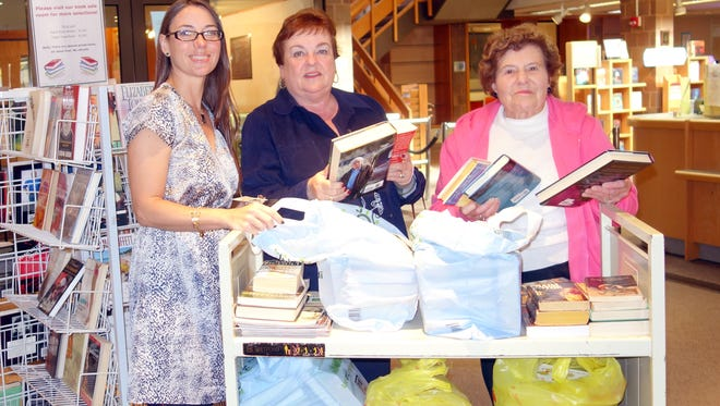 (From left) Brandi Grosso, head librarian at Vineland Public Library, joins Woman's Club of Vineland members Norene Ritter and Annette Lipartito to count and check donations for the library's upcoming book sale.