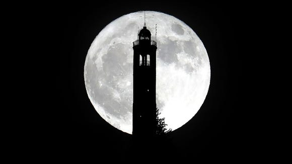 The super moon rises above the lighthouse of San Maurizio