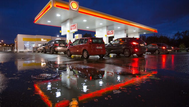Customers fill up at a Shell gas station operated by Royal Dutch Shell Plc as rain falls at night in Moscow on Sept. 30.