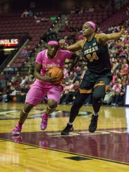 Shakayla Thomas (20) drives past a defender as the