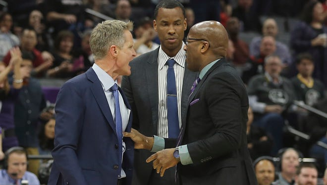 Golden State Warriors assistant coach Mike Brown, right, restrains Warriors head coach Steve Kerr, left, as he yells at official Bill Spooner who had ejected Kerr during the second half of an NBA basketball game against the Sacramento Kings.