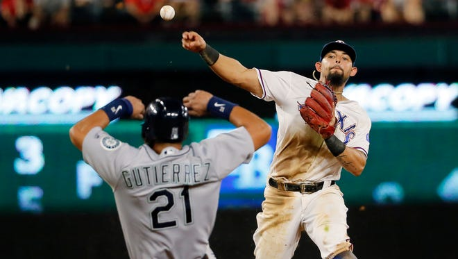 Texas Rangers second baseman Rougned Odor throws to first after forcing Seattle Mariners' Franklin Gutierrez (21) at second in the seventh inning of a baseball game, Tuesday, Aug. 30, 2016, in Arlington, Texas. The Mariners Kyle Seager was safe at first.